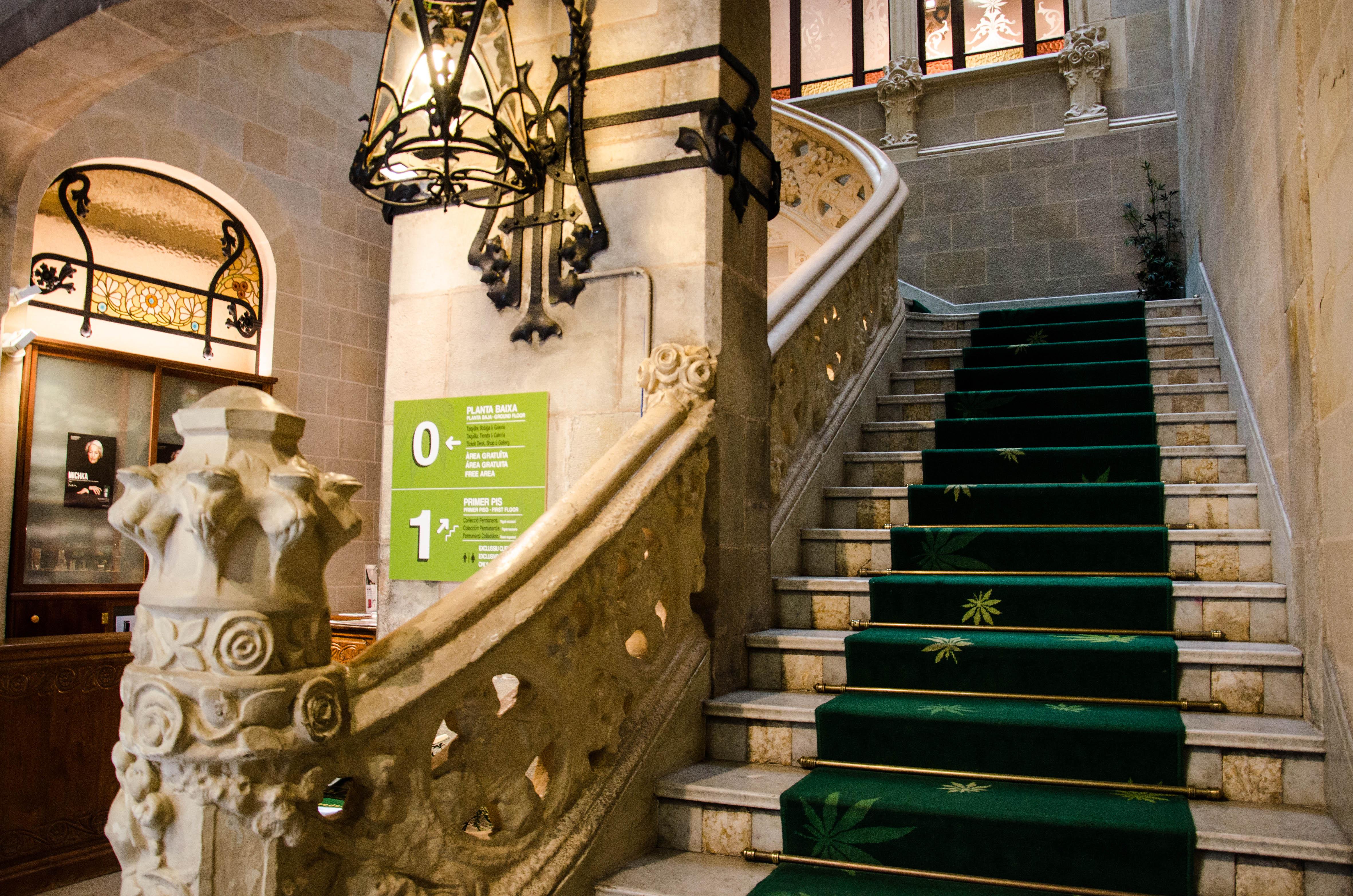 Un escalier de marbre, aux rambardes sculptées, mène à l'exposition.